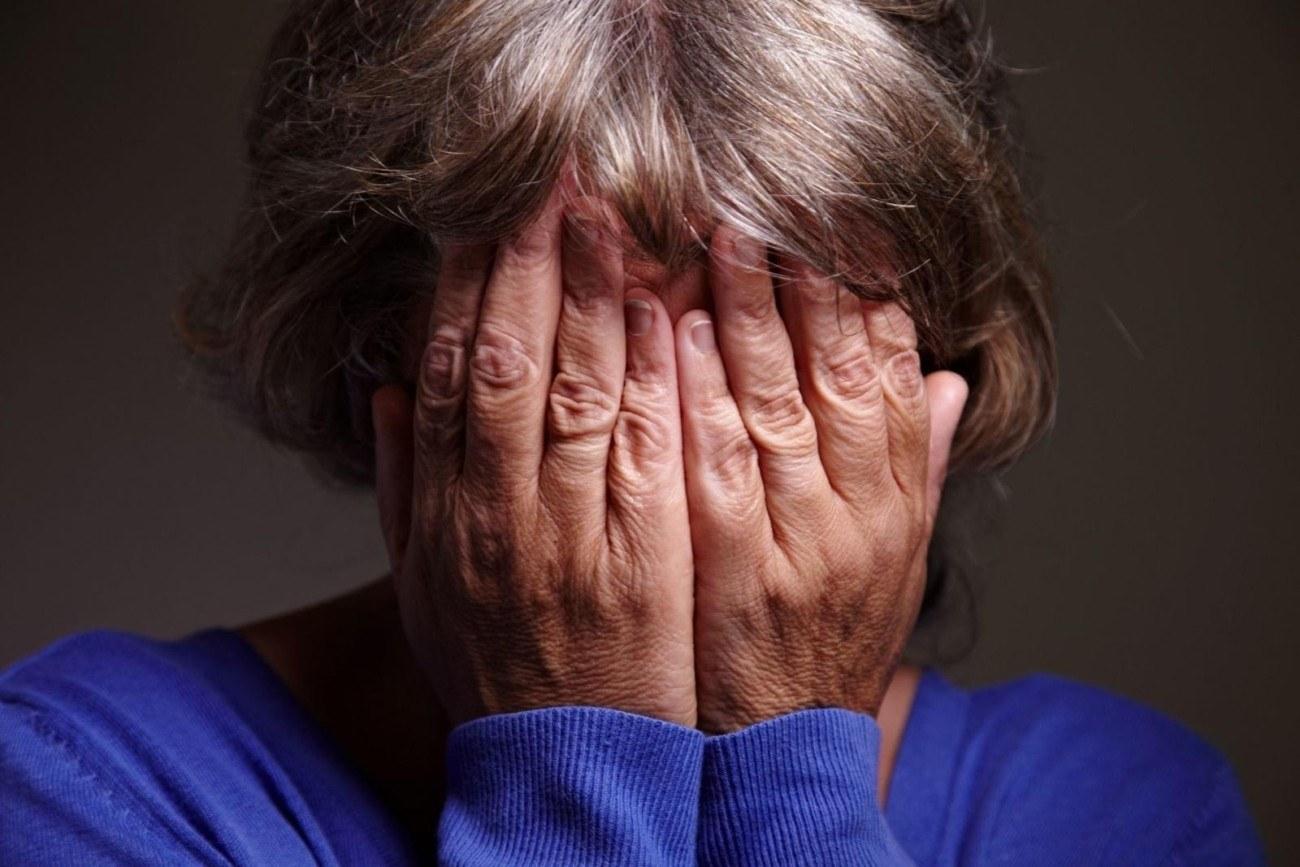 пенсионерка закрывает лицо